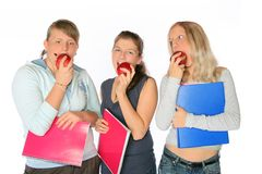 Healthy Meeting. Three teenage girls eating apples when holding their notebooks Royalty Free Stock Photography