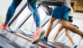Healthy man and woman running on a treadmill in a gym royalty free stock image