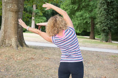 Healthy middle aged woman doing fitness stretching outdoors royalty free stock photo