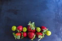Healthy mix fruits on a dark slates royalty free stock photography