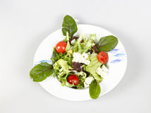 Healthy mix salad. Upper view of an isolated appetissing lettuce salad with cheese and tomato on white background Royalty Free Stock Image