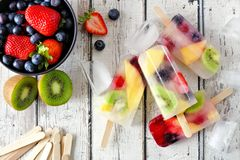 Healthy mixed fruit summer popsicles, table scene over white wood. Healthy mixed fruit summer popsicles. Top view table scene on a white wood background stock photo