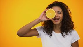Healthy mixed-race girl holding orange, vitamins and wellness, skincare concept. Stock footage stock video footage