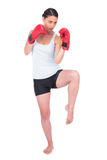 Healthy model with boxing gloves kicking Royalty Free Stock Photo