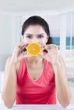 Healthy model holds an orange slice Stock Image