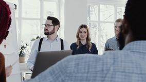Healthy modern workplace. Young Caucasian coach businessman leading discussion at office meeting slow motion RED EPIC. Multiethnic smiling business colleagues stock video footage
