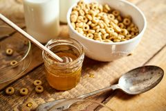 Healthy morning breakfast bowl full of honey flakes with honey dipper and milk on wooden table royalty free stock photos