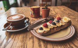 A healthy morning breakfast of coffee and banana toast on sourdough royalty free stock photography