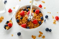 Healthy Morning Breakfast honey Corn flakes with fresh fruits of Raspberry, blueberries and pouring milk in bowl. Healthy Morning Breakfast honey Corn flakes Stock Images