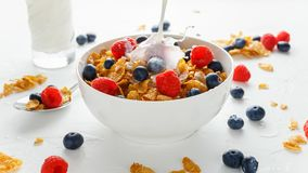 Healthy Morning Breakfast honey Corn flakes with fresh fruits of Raspberry, blueberries and pouring milk in bowl. Healthy Morning Breakfast honey Corn flakes Stock Image