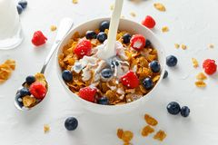 Healthy Morning Breakfast honey Corn flakes with fresh fruits of Raspberry, blueberries and pouring milk in bowl. Healthy Morning Breakfast honey Corn flakes Royalty Free Stock Photo