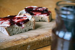 Healthy morning breakfast made of jam on the white bread, put on the vintage wooden chopping board Stock Image