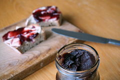 Healthy morning breakfast made of jam on the white bread, put on the vintage wooden chopping board Royalty Free Stock Photo