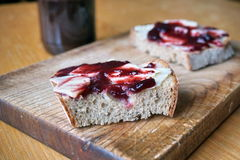 Healthy morning breakfast made of jam on the white bread, put on the vintage wooden chopping board Royalty Free Stock Photos