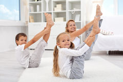 Healthy morning stretching. Women with kids doing gymnastic exercise at home Stock Photos