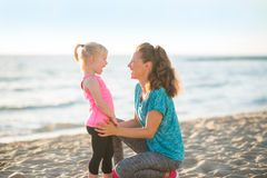 Healthy mother and baby girl on beach in the eveni Stock Photo