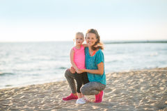 Healthy mother and baby girl on beach in the eveni Stock Photos
