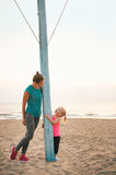 Healthy mother and baby girl on beach in evening Royalty Free Stock Photography