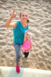Healthy mother and baby girl on beach pointing Stock Photos