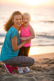 Healthy mother and baby girl on beach Stock Images
