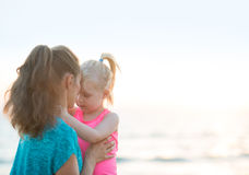 Healthy mother and baby girl hugging on beach Stock Photography