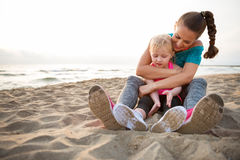 Healthy mother and baby girl hugging on beach Royalty Free Stock Photo