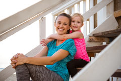Healthy mother and baby girl hugging on stairs Stock Photo