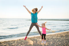 Healthy mother and baby girl jumping on beach. In the evening Royalty Free Stock Photography