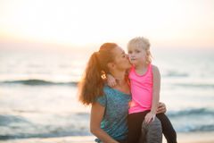 Healthy mother and baby girl kissing on beach Royalty Free Stock Image