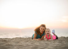 Healthy mother and baby girl laying on beach Royalty Free Stock Photos