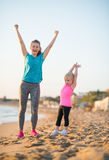Healthy mother and baby girl rejoicing on beach Stock Image