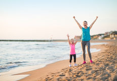 Healthy mother and baby girl rejoicing on beach Royalty Free Stock Photo
