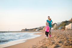 Healthy mother and baby girl running on beach Royalty Free Stock Photography