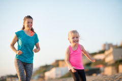 Healthy mother and baby girl running on beach Royalty Free Stock Images