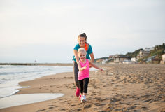 Healthy mother and baby girl running on beach Stock Photos