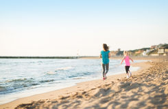 Healthy mother and baby girl running on beach Royalty Free Stock Photos