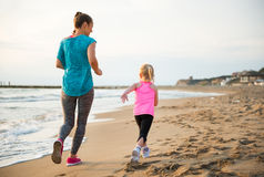 Healthy mother and baby girl running on beach Stock Images