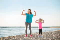 Healthy mother and baby girl showing biceps on bea Royalty Free Stock Photos