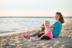 Healthy mother and baby girl sitting on beach Royalty Free Stock Photos