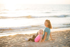 Healthy mother and baby girl sitting on beach Royalty Free Stock Images