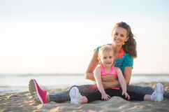 Healthy mother and baby girl sitting on beach Stock Photo