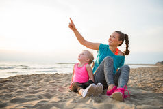 Healthy mother and baby girl sitting on beach Stock Photos