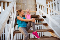 Healthy mother and baby girl sitting on beach Royalty Free Stock Photo