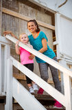 Healthy mother and baby girl standing on stairs Stock Photo