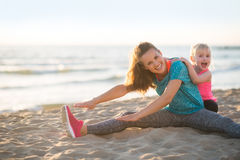 Healthy mother and baby girl stretching on beach Stock Photo
