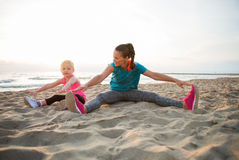 Healthy mother and baby girl stretching on beach. In the evening Royalty Free Stock Images
