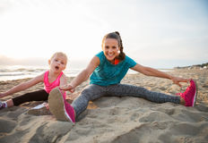 Healthy mother and baby girl stretching on beach Royalty Free Stock Photography