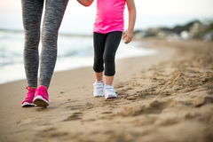 Healthy mother and baby girl walking on beach. In the evening Royalty Free Stock Images