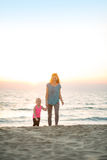 Healthy mother and baby girl walking on beach Stock Image