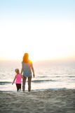 Healthy mother and baby girl walking on beach Stock Photography